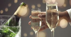 Festive bubbles in a glass of sparkling wine. Bubbles going up in thin flute champagne glasses on a holiday table with a bottle of champagne in ice basket stock footage