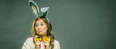 Festive bunny and eggs season. happy modern woman in Easter bunny ears isolated on grey background stock images