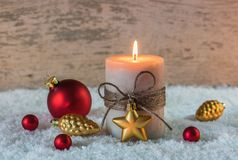 Festive Christmas holiday celebration candle on snow with xmas red and golden ornaments decoration Stock Photo