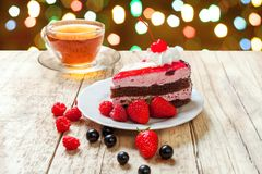 A festive cake with cherries. And berries against a bright colored bokeh. Festive treat for your birthday or Christmas Stock Photos