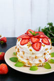 A festive cake with fresh strawberries, cream, decorated with mint leaves on a black background. Stock Photography
