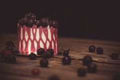 Festive cake with the fruits of cherry on a rustic wooden table on a dark background. close up copy space. vintage pattern on. Dessert tartlet. birthday holiday royalty free stock photography