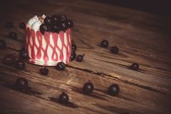 Festive cake with the fruits of cherry on a rustic wooden table on a dark background. close up copy space. vintage pattern on. Dessert tartlet. birthday holiday royalty free stock images