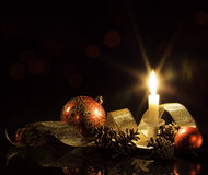 Festive candle, baubles and ribbon Stock Photo