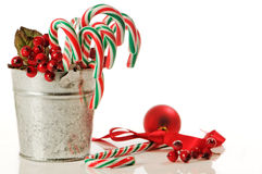 Festive Candy Canes. Bucket of festive Christmas candy canes with decorations on white background Stock Photos