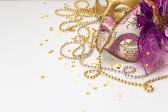 Festive Carnival Background with masks, beads and copy space. Festive Carnival Background with masks and beads and copy space. Purple carnival masks on a white Royalty Free Stock Photo