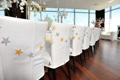 Festive chairs. Table and chairs in white decorated to celebrate anniversary of  restaurant Stock Image