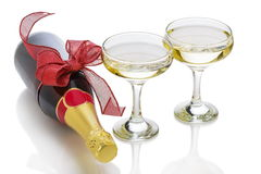 Festive champagne bottle. With red bow knot and two glasses over white background Stock Photo