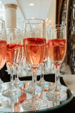Festive champagne flutes filled with sparkling wine and floating strawberries romantic twinkling party lights. Festive champagne flutes filled with sparkling Royalty Free Stock Images