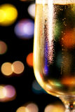 Festive Champagne Toast. A festive champagne toast with close-up of glass.  Background of colourful lights on black.  Shallow focus on condensation on glass Royalty Free Stock Images