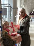 Festive Charity Donation Boxes. Little girl and her mother are giving donation boxes to a charity for christmas stock photography