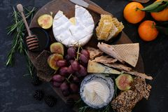 Cheeseboard with a variety of cheeses, crackers, fruit, honey, rosemary sprigs and chutney. Festive cheeseboard with a variety of cheeses, crackers, fruit, honey Royalty Free Stock Image