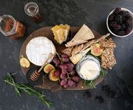 Cheeseboard with a variety of cheeses, crackers, fruit, honey, rosemary sprigs and chutney. Festive cheeseboard with a variety of cheeses including brie and Stock Image