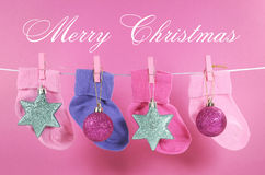 Festive childrens baby stockings with Merry Christmas sample text. Festive childrens baby stockings hanging from pegs on a line with Merry Christmas greeting and Royalty Free Stock Photography