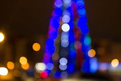 Blurred colored circles on a light holiday background. A festive Christmas background with a bokeh of Christmas tree lights. Blurred colored circles on a light royalty free stock photography