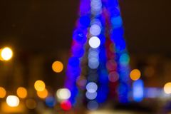 Blurred colored circles on a light holiday background. A festive Christmas background with a bokeh of Christmas tree lights. Blurred colored circles on a light royalty free stock image