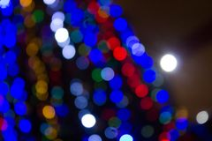 Blurred colored circles on a light holiday background. A festive Christmas background with a bokeh of Christmas tree lights. Blurred colored circles on a light royalty free stock photo