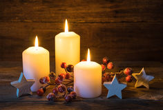 Festive Christmas background with burning candles, stars and red berries decoration. Royalty Free Stock Photo