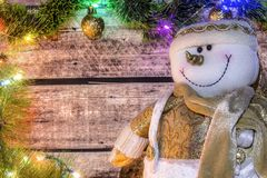 Festive Christmas background of dark old wooden boards, fir-tree, snowman and luminous garland with colored lights and Christmas b. Alls for a banner, postcard royalty free stock photography