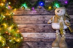 Festive Christmas background of dark old wooden boards, fir-tree, snowman and luminous garland with colored lights and Christmas b. Alls for a banner, postcard stock image