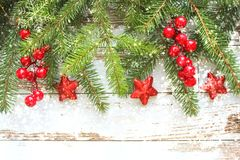 Festive Christmas background. Fir branches with red berries and stars on white wooden background . Copy space. New year`s greeting card royalty free stock images