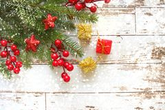 Festive Christmas background.Gift box with white bow Fir branches with red berries and stars on white wooden background . royalty free stock photo