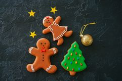 Festive Christmas background, Gingerbread man and girl Cookies,. Fir tree,  stars and ball on a black stone background. Top view with copy space Royalty Free Stock Image