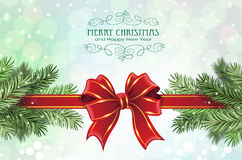 Festive Christmas background. Red bow and ribbon with fir tree branches on a sparkling  holiday background. Festive Christmas background Royalty Free Stock Photos