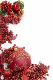 Festive christmas berries. A vibrant red christmas border with berries and a bauble Royalty Free Stock Images