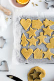 Festive Christmas Biscuits on Baking Tray surrounded by Cookie Cutters and Ingredients Royalty Free Stock Photos