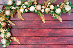 Festive Christmas border in gold, green and white. With assorted baubles and tree decorations on evergreen foliage arranged as a corner on mahogany stained Royalty Free Stock Photography