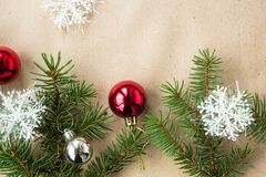 Festive christmas border with red and silver balls on fir branches and snowflakes on rustic beige background Royalty Free Stock Photography
