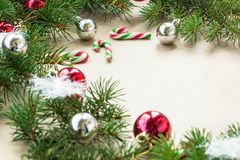 Festive christmas border with red and silver balls on fir branches and snowflakes on rustic beige background. With copyspace stock photos
