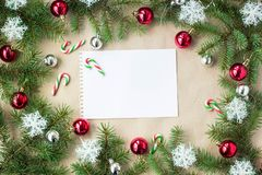 Festive christmas border with red and silver balls on fir branches and snowflakes on rustic beige background. With copyspace and pen stock image