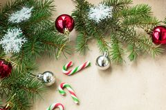 Festive christmas border with red and silver balls on fir branches and snowflakes on rustic beige background. With copyspace and pen stock photography