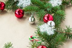 Festive christmas border with red and silver balls on fir branches and snowflakes on rustic beige background. With copyspace and pen royalty free stock images
