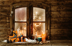 Festive Christmas cabin window. Festive wooden Christmas cabin window with gift-wrapped colorful orange presents, burning candles and decorations in winter snow Stock Photo