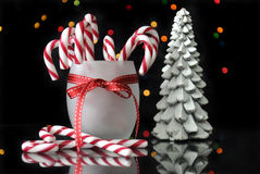 Festive Christmas candy canes and trees on reflective table Stock Photo