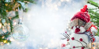 Festive Christmas card. With snowman, Christmas bauble and fir branches on winter background stock photography