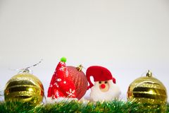 Red and two gold christmas balls, and Christmas decoration on a white background. Festive, Christmas card,red ball ,two gold balls,toy Snta and Christmas Royalty Free Stock Photos