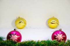Two purple Christmas balls and two golden balls behind them and Christmas accessorieson a white background. Festive, Christmas card,two Purple balls,two golden Royalty Free Stock Photo