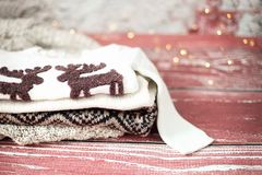 Festive Christmas composition. Winter warm sweaters folded and packed in grey vintage suitcase. Red background Stock Images