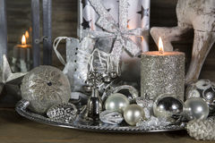 Festive christmas decoration in silver with burning candles. Royalty Free Stock Image