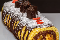 Festive Christmas delicious cake with chocolate. Delicious choco. Late rolls with fruits, beautifullly decorated with candy and coconut for Christmas meal Stock Photography