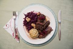 Festive Christmas dinner in Austria. Typical seasonal venison filet dish decorated with red cabbage and chestnut, bread dumpling and cranberry sauce, prepared on Stock Photo