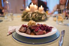 Festive Christmas dinner in Austria. Typical seasonal venison filet dish medium rare, decorated with red cabbage and chestnut, bread dumpling and cranberry sauce Royalty Free Stock Images