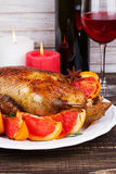 Festive Christmas duck baked with grapefruits and rosemary, glass of wine and candles. Royalty Free Stock Photography