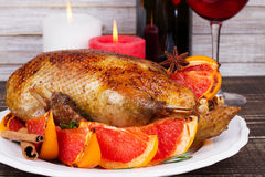Festive Christmas duck baked with grapefruits and rosemary, glass of wine and candles. Stock Photography