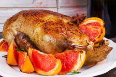 Festive Christmas duck baked with grapefruits and rosemary, glass of wine and candles. Stock Photo