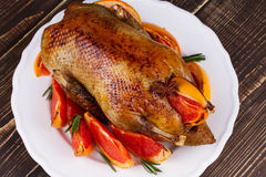 Festive Christmas duck baked with grapefruits and rosemary, glass of wine and candles. Stock Photos